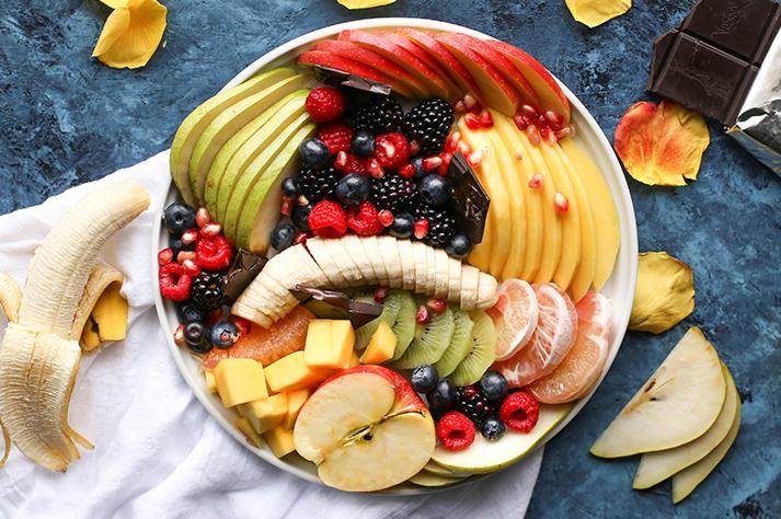 Tuoreita hedelmiä valkoisella lautasella, mitkä ovat hyviä kaliumin lähteitä ja auttavat päivittäisen kaliumtarpeen täyttymiseen