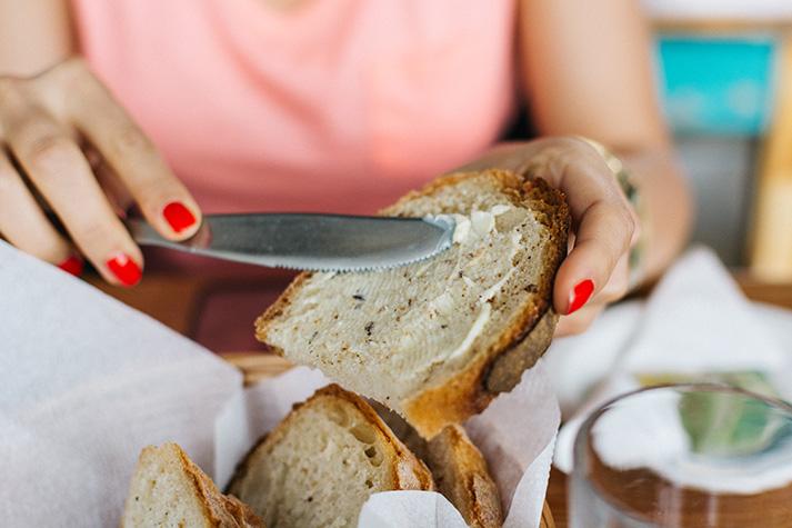 Nainen voitelee leivälle Alentaja-levitettä, joka alentaa kolesteroliarvoja.